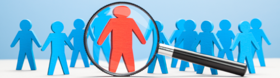 A magnifying glass is focused on the single red figure in a group of otherwise blue paper figures standing on a white surface.