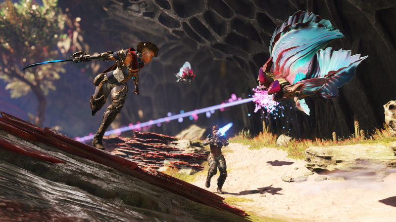 An alien creature is firing a weapon at two human characters. One of the characters is running and has a sword at her side. The other is firing a weapon back at the creature.