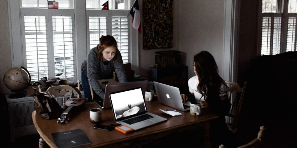 Two women working on laptops at a table; Photo by Andrew Neel on Unsplash