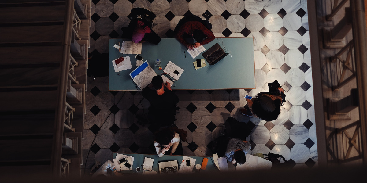 birds eye view of students in library on laptops; Photo by Emre Gencer on Unsplash