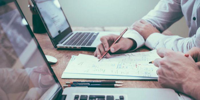 man writing on notepad next to laptop