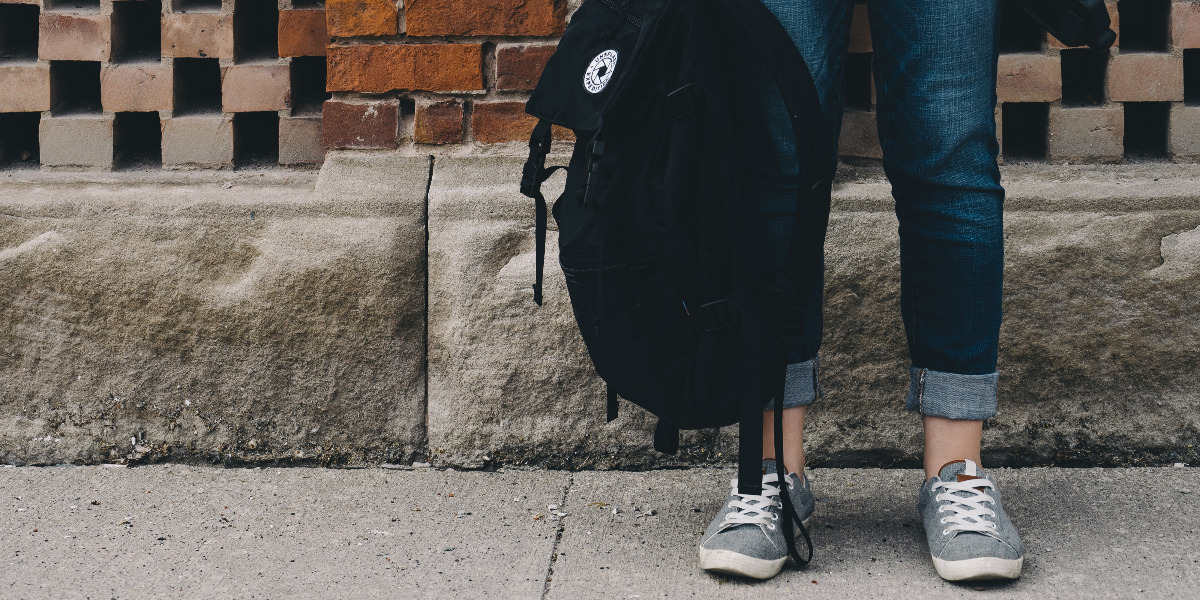 student with backpack; Photo by Scott Webb on Unsplash