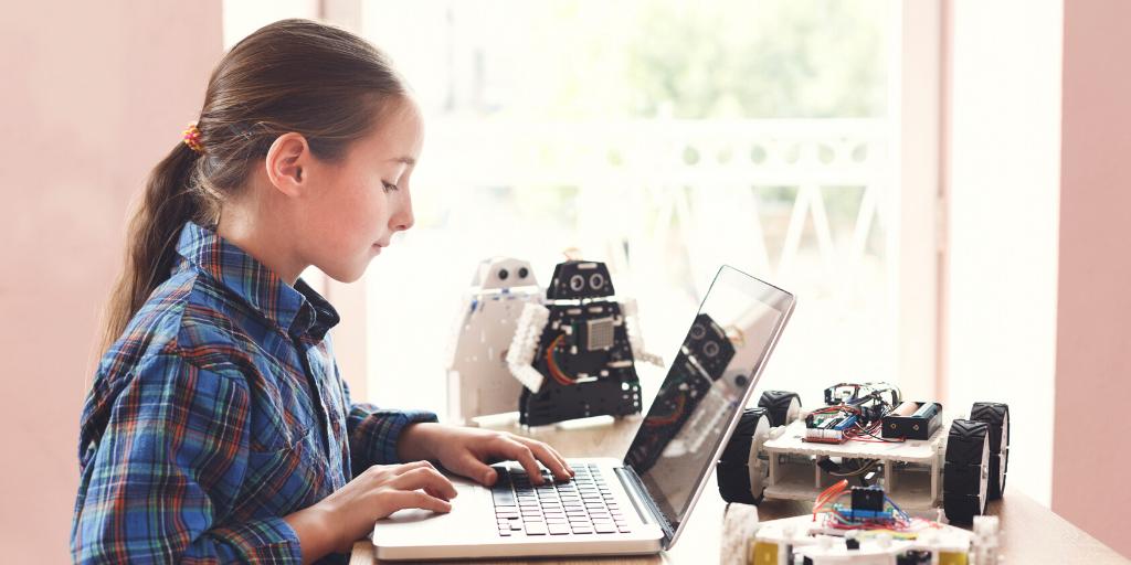 student at laptop programming robot