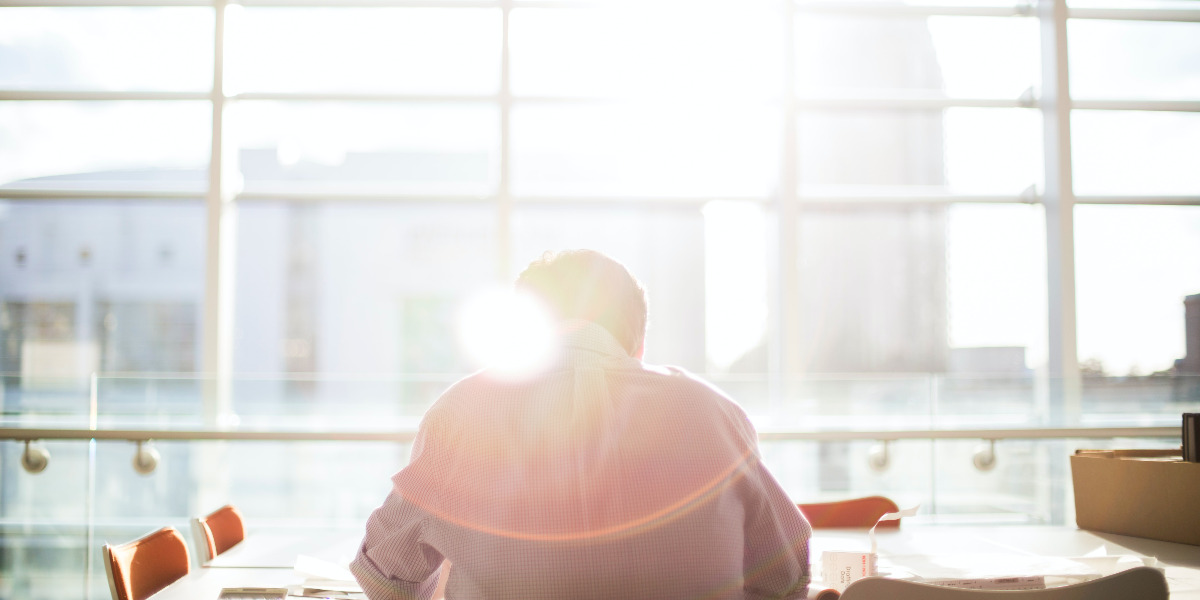 man with back to camera in office with sun coming through windows