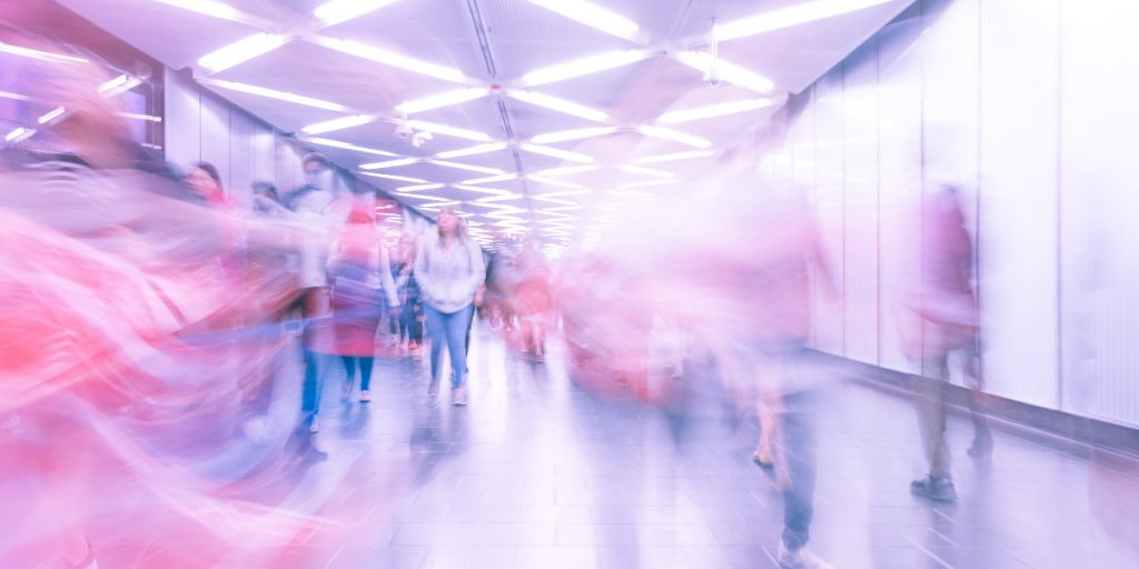 blurry photo of people passing through Fulton Street subway station in NYC