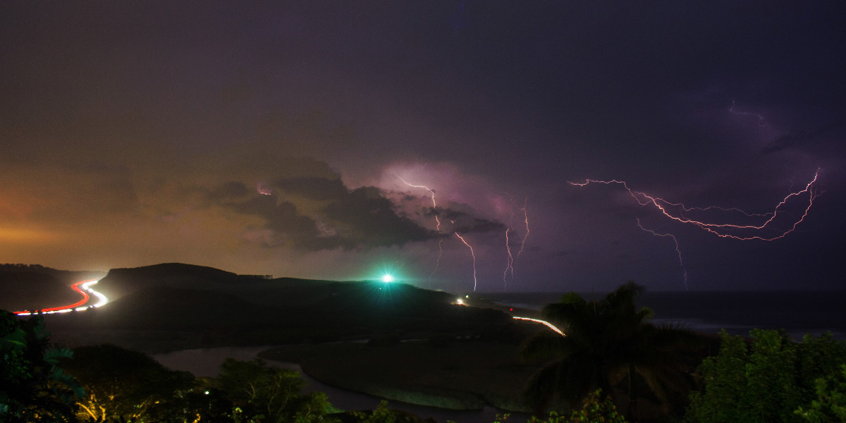 lightning strike at night over mountains with highway