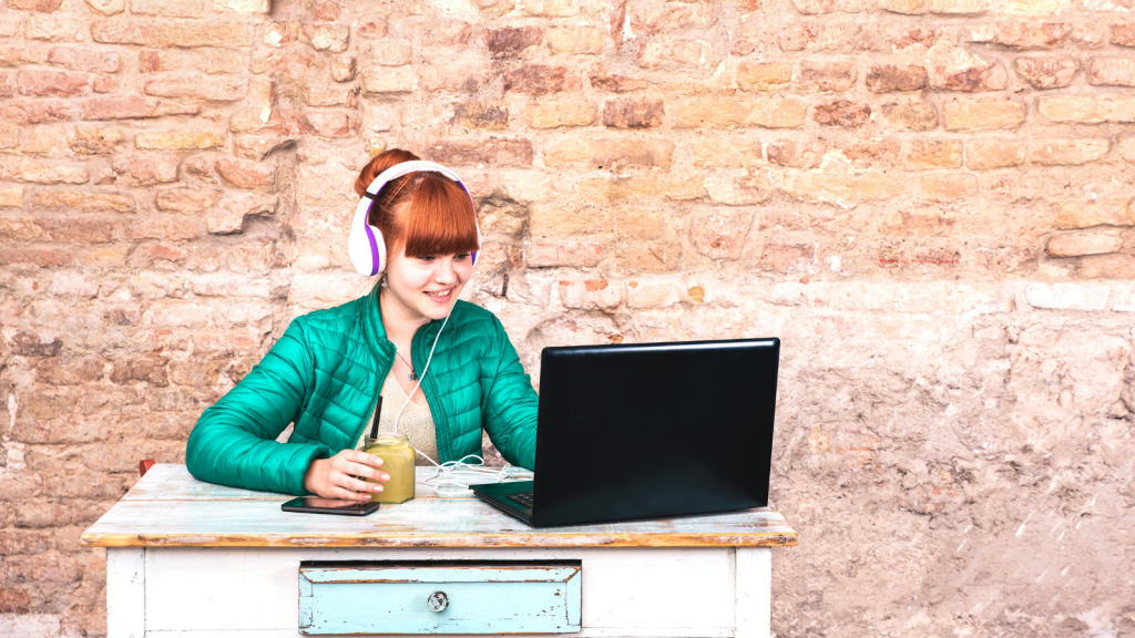 woman sitting at table with headphones and laptop