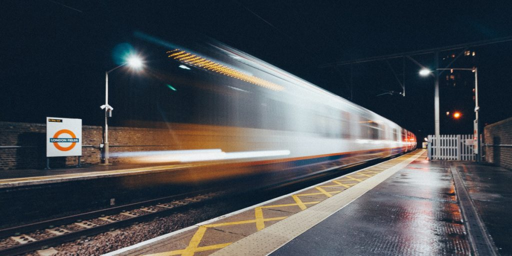 tube train speeding past in a blur at station at night