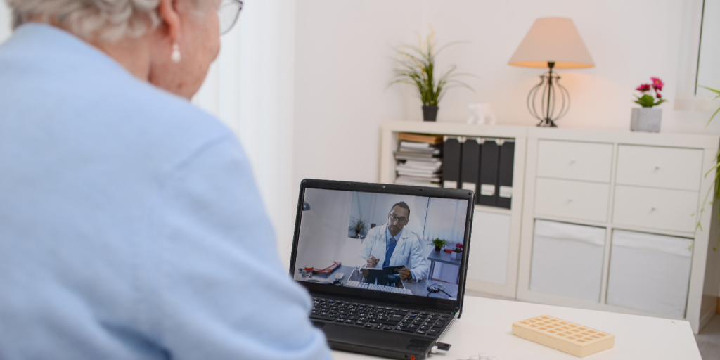 older woman doing telemedicine visit with doctor on laptop