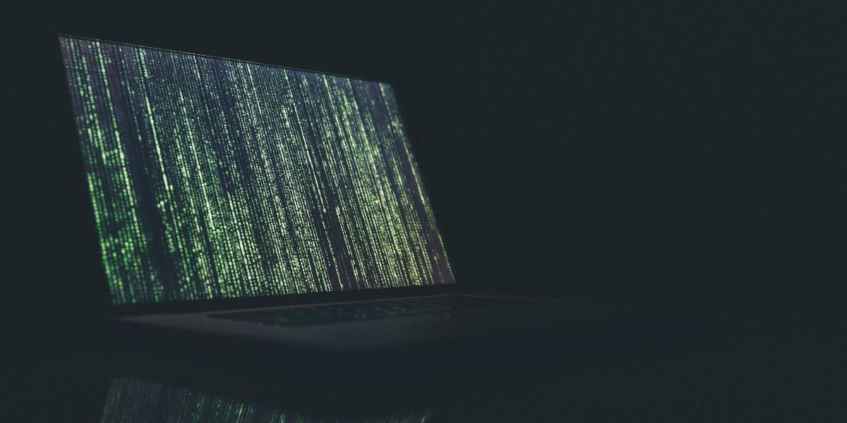 laptop in dark with code on screen; Photo by Markus Spiske on Unsplash