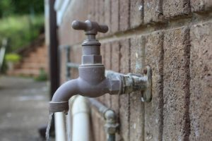 water tap coming out of brick wall