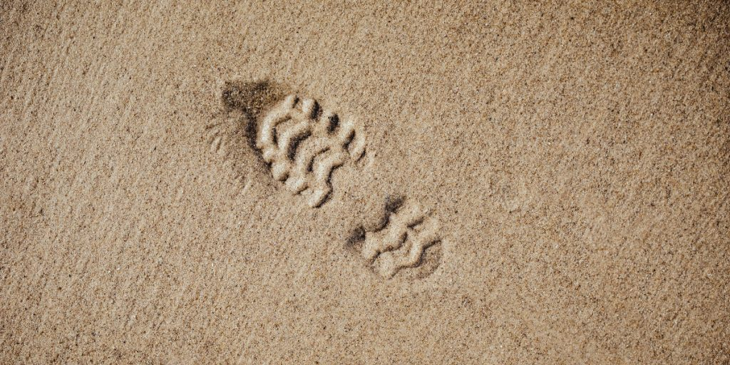 bootprint in sand; photo by Bernard Hermant via Unsplash