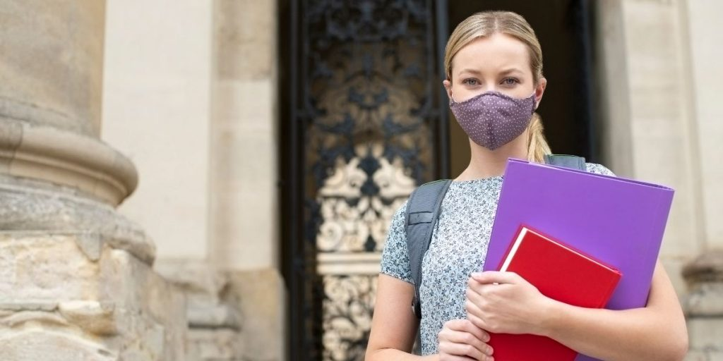female student with mask holding books outside university building