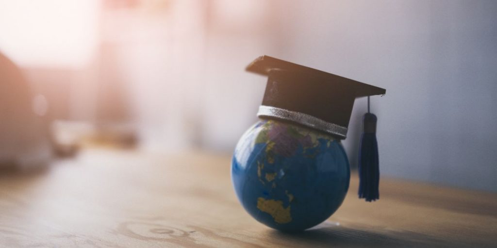 tiny globe on a desk with graduation cap