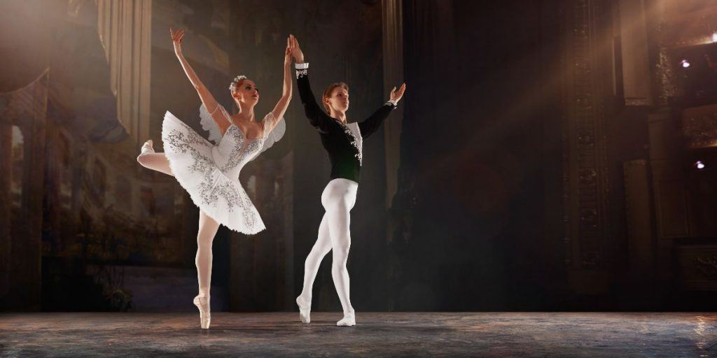 woman and man ballerinas perform on stage