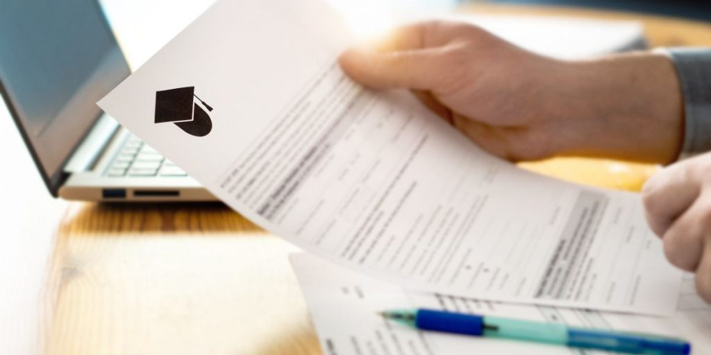 hands hold paper college application form next to an open laptop