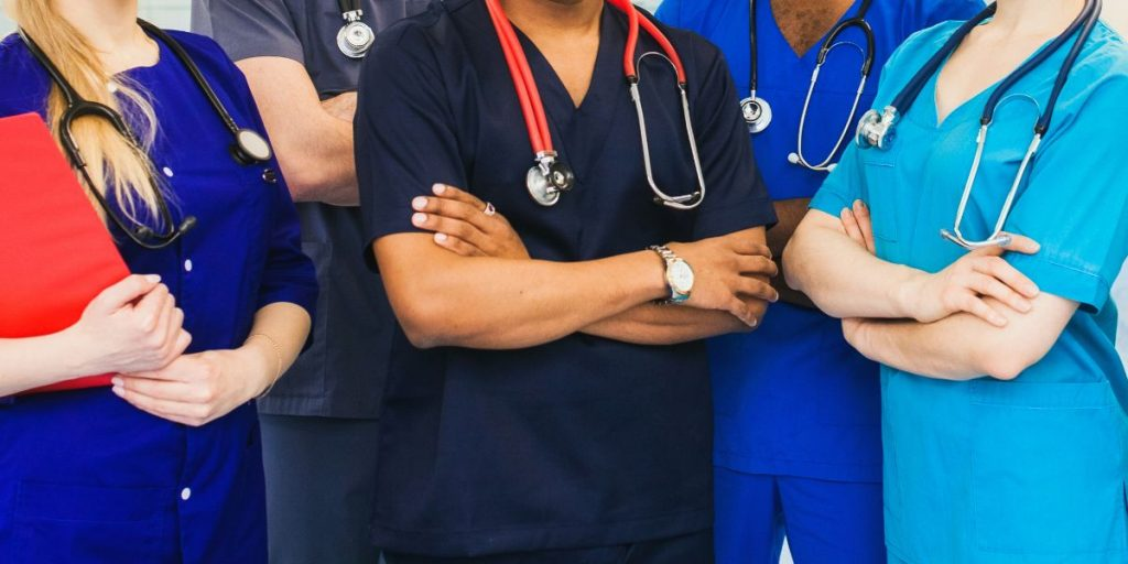 hospital staff standing close together with arms crossed torsos only