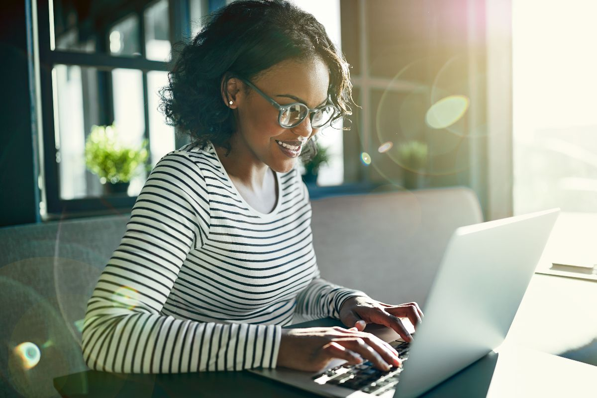 woman on laptop excitedly typing at desk