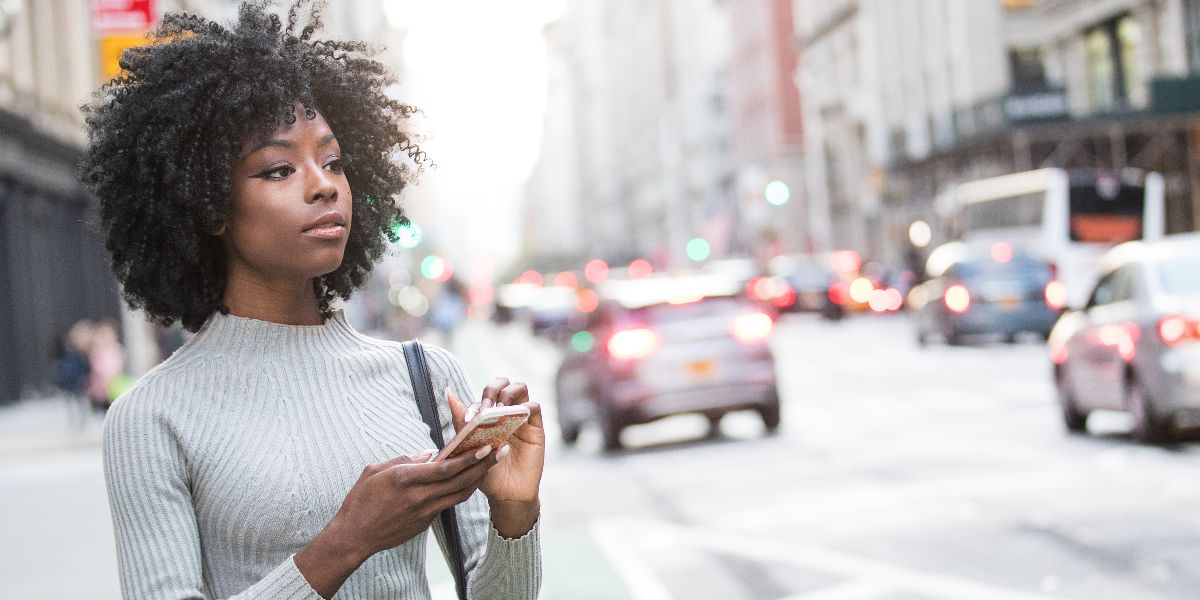 woman checking her smart phone standing on busy city street