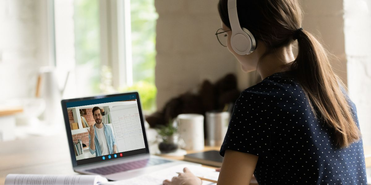 female student sitting at laptop at home with headphones listening to lecture