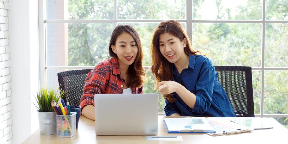 two women working on laptop