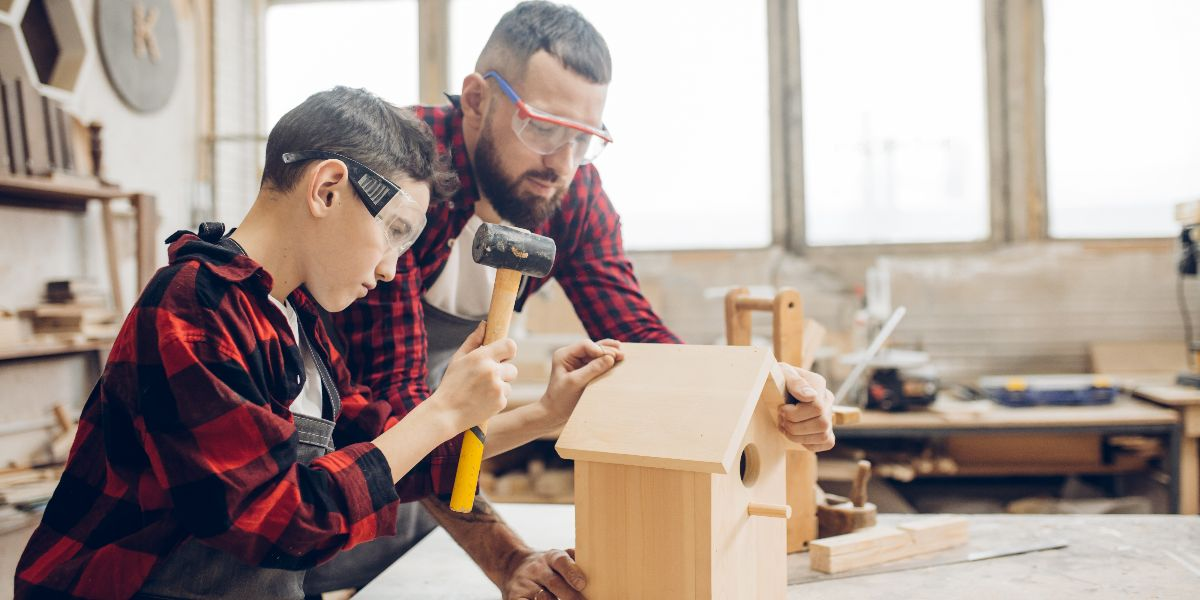 man and son work in woodshop to build birdhouse