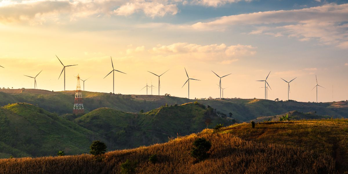 windmills over a green hill with orange sunset