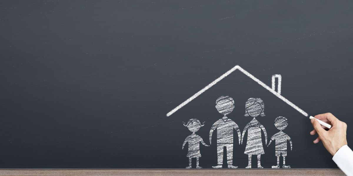 hand with chalk drawing family and house on chalkboard