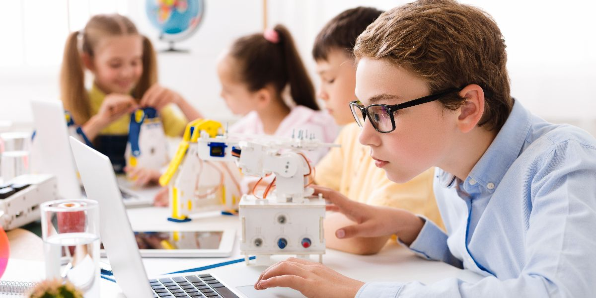 young boy on laptop assembling robot with classmates in background
