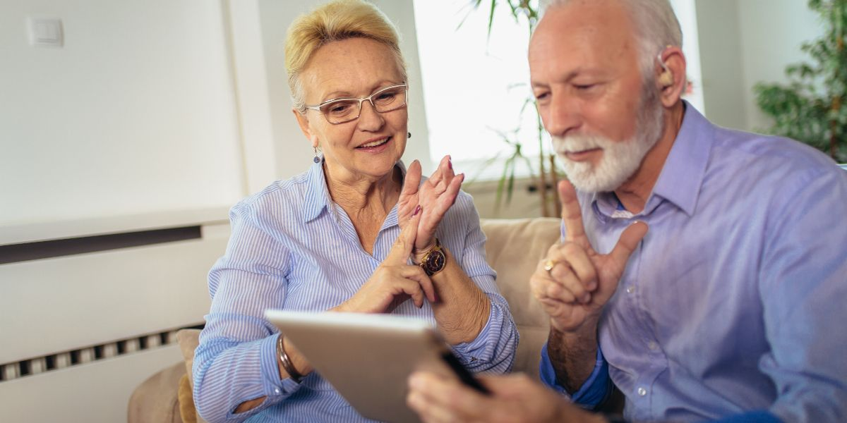 elderly couple signing on tablet