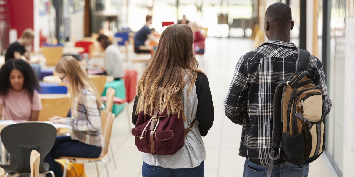 two students walking away from camera through a campus common area