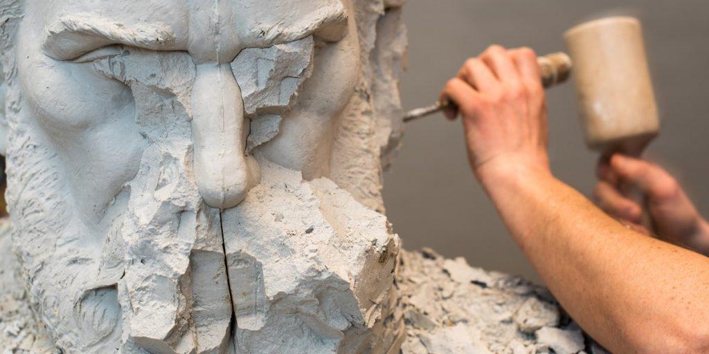 のみと槌で彫刻を彫る画像