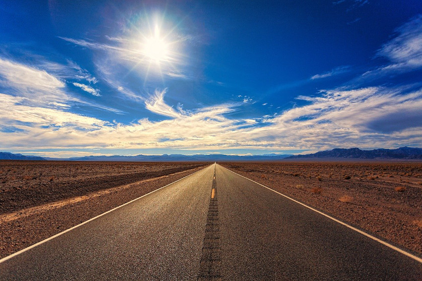 Photo of a road through the desert with sunshine and clouds, via Pixabay https://pixabay.com/photos/road-sky-desert-landscape-nature-3133502/