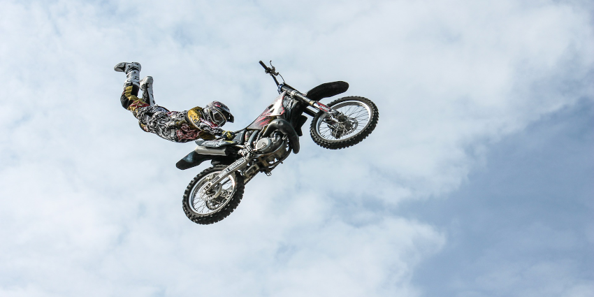 person on motorcycle doing a jump stunt with clouds in background