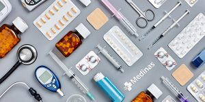 Directly above flat lay flat lay shot of various medical supplies. Full frame shot of medicines placed with syringes and diagnostic tools. All are on gray background.