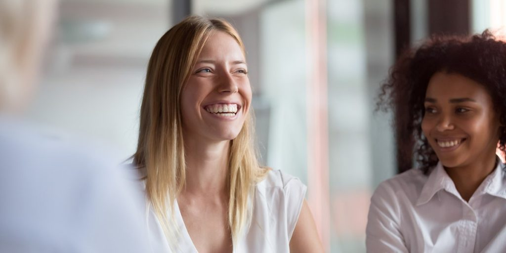 A woman smiling and laughing with a colleague in a business meeting