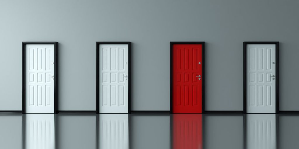 Three white doors and one red door against a grey wall