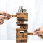 Two businessman playing a game with a balancing tower of blocks with stacks of coins on top