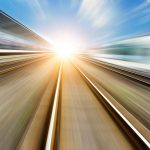 A high speed perspective image of a railway track leading into the sun on the horizon
