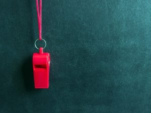 A red whistle on a red cord hanging in front of a blackboard