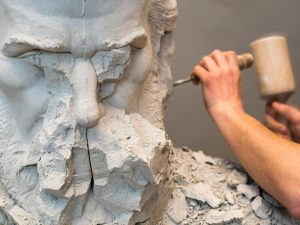 A sculptor uses a hammer and chisel to add detail to a rough statue of a man