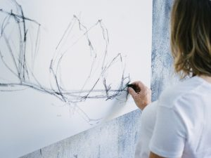 A female painter sketching a preparatory drawing with charcoal on canvas