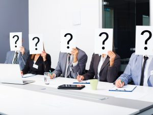 A group of business people in a meeting holding question mark signs over their faces