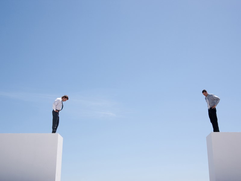 Two businessman standing on opposite sides of a gap and looking down