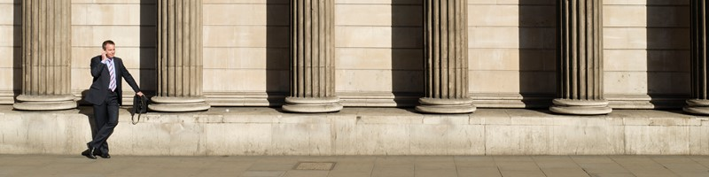 City worker talking on a mobile phone outside the imposing facade of the Bank of England