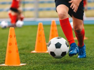 A soccer player conducts practice drills between a series of orange pylons