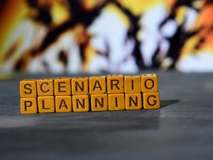 "A row of wooden blocks on a table spells out ""scenario planning"""