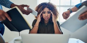 A stressed businesswoman is overwhelmed with too much work
