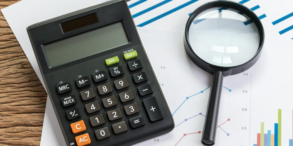 Calculator and magnifying glass on a pile of graphs and charts on a wood table