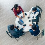 Aerial view of a small team collaborating at a desk